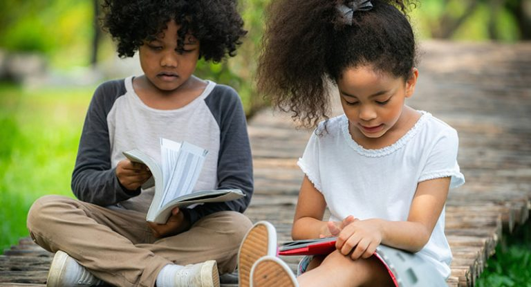 Happy little boy and girl reading in the park